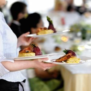 Server carrying plates of food.