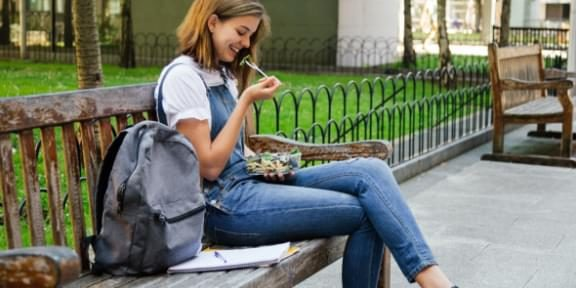 Female college student eating a boxed salad.