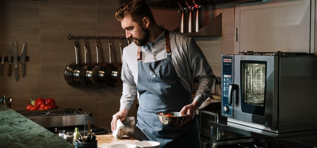 Chef (bearded male) working.