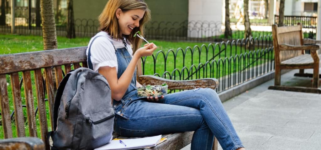A student eating a boxed lunch.
